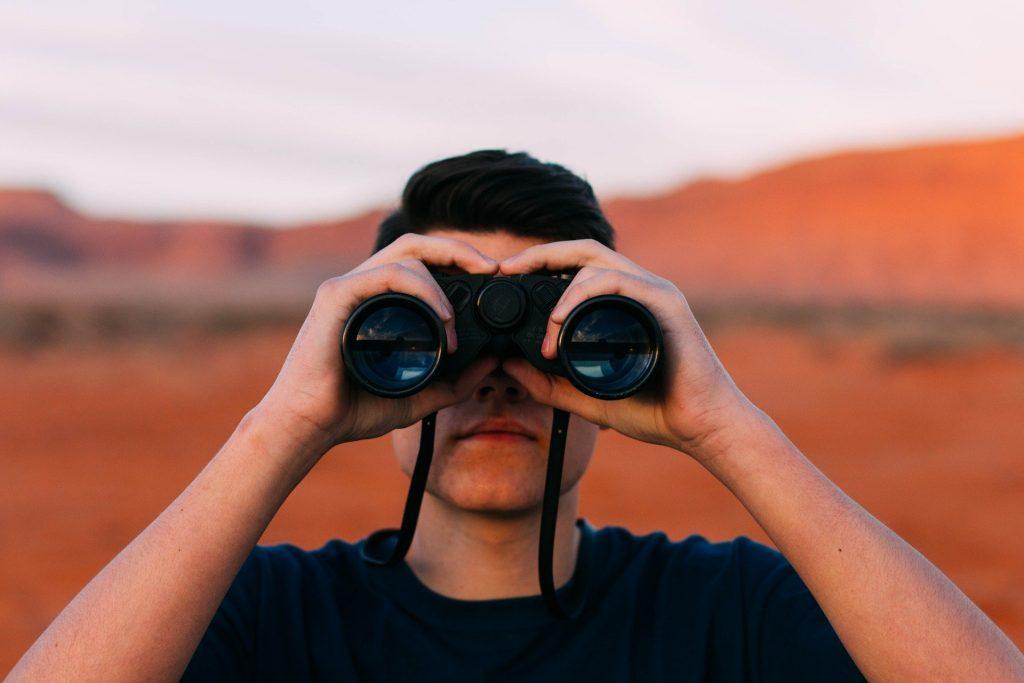 Mann blickt durch Fernglas