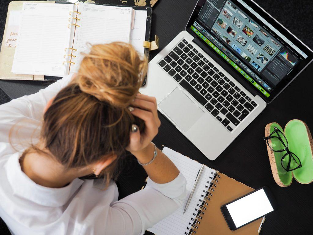 Frau sitzt gestresst vor Laptop