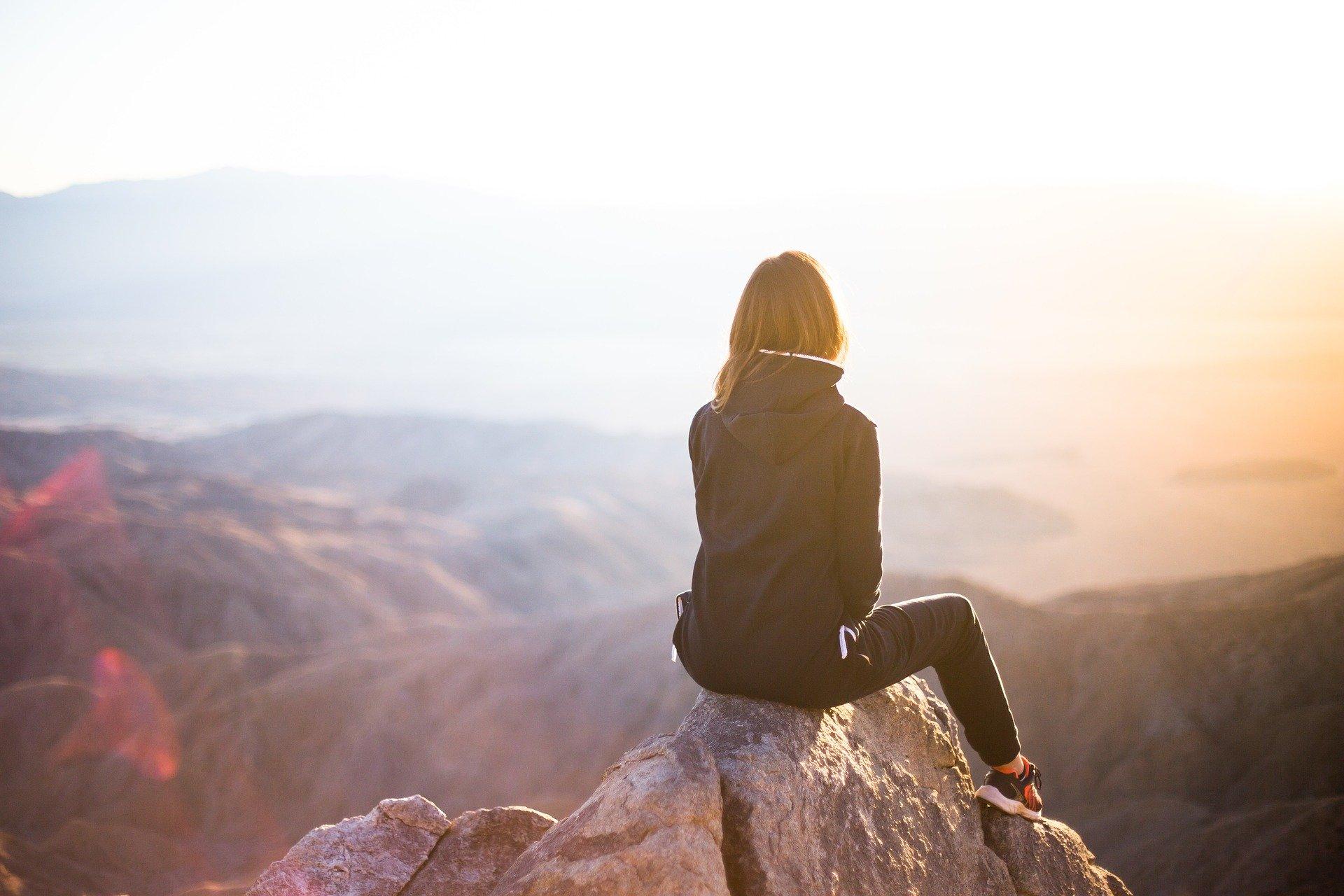 Frau sitzt auf Berg